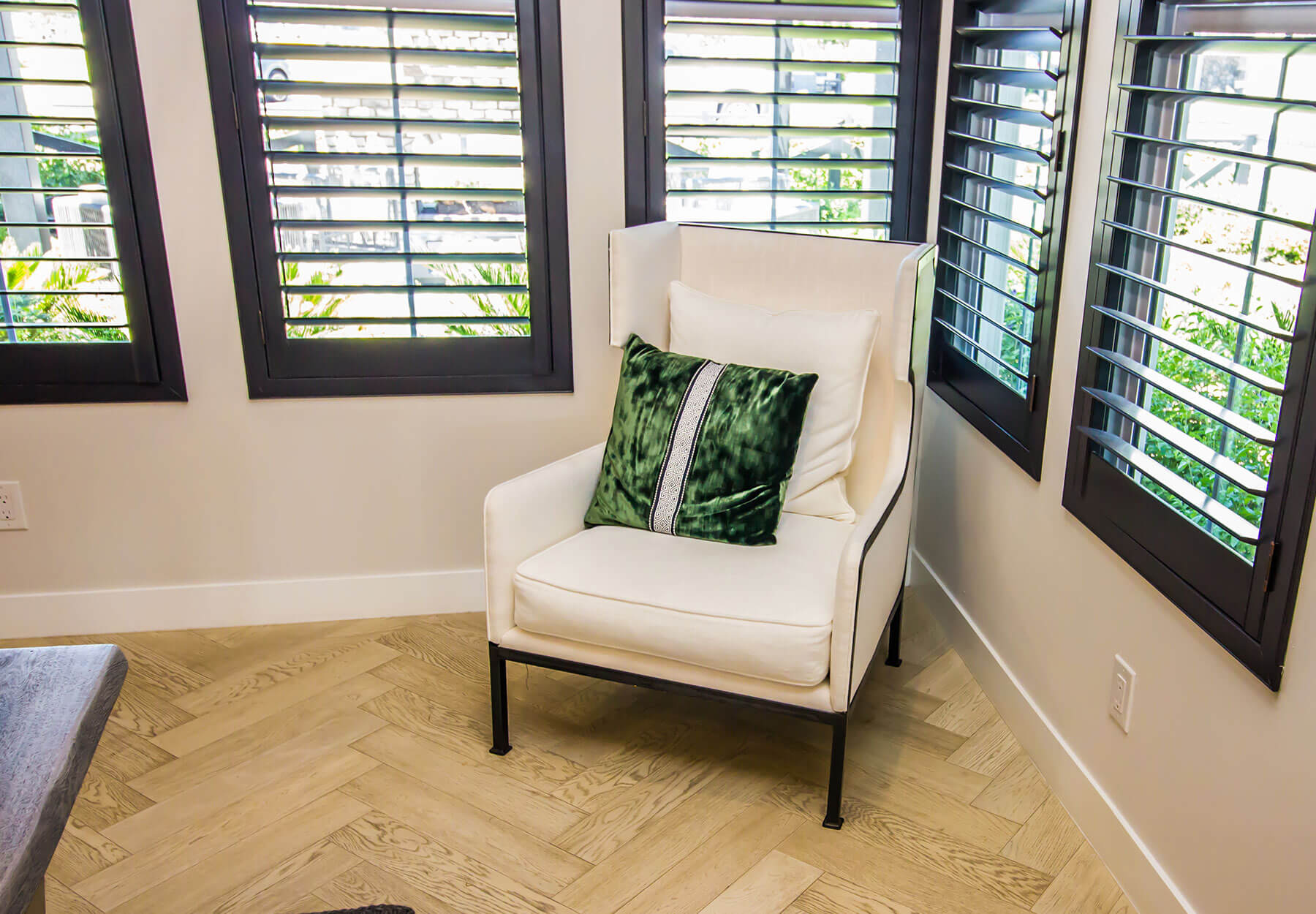 A room with a chair and wood shuttered windows