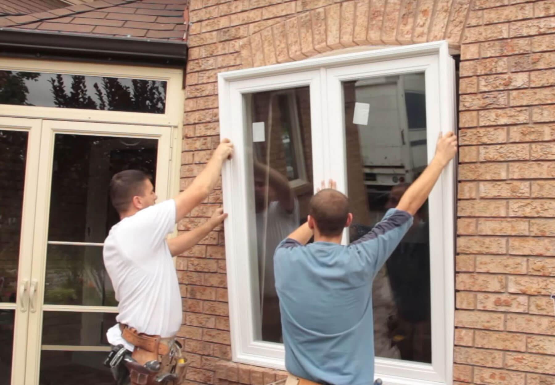 Two men installing a window