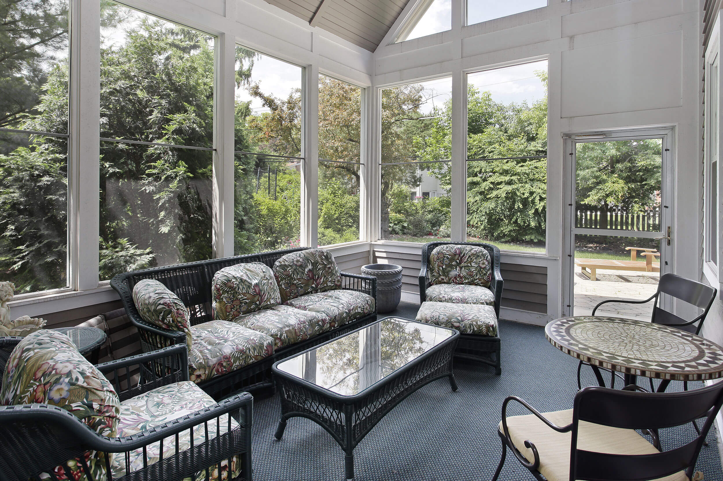 A view from inside a furnished sunroom